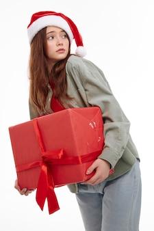 Девушка в подарочной коробке шляпы санта смотрит в сторону студия. фото высокого качества