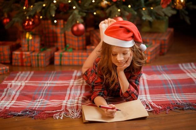 クリスマスツリーの近くに横たわって、サンタの手紙を書いているサンタの帽子の少女