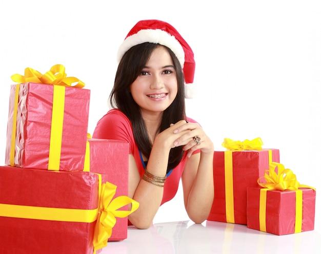 Девушка в новогодней шапке с сумкой, полной рождественского подарка
