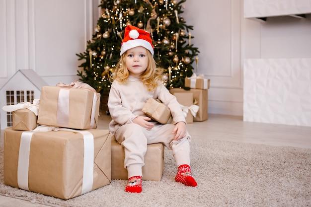 クリスマスツリーの背景にクリスマスプレゼントとサンタ帽子の女の子。自宅でクリスマスプレゼントを持った子供。冬の休日のための装飾された家。ソフトフォーカス