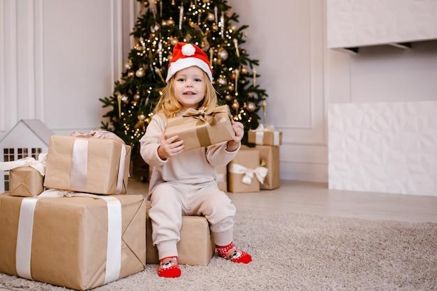 Девушка в шляпе санты с рождественским подарком на фоне елки.