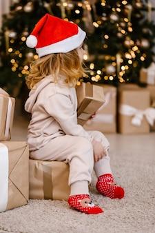 クリスマスツリーの背景にクリスマスプレゼントとサンタ帽子の女の子。