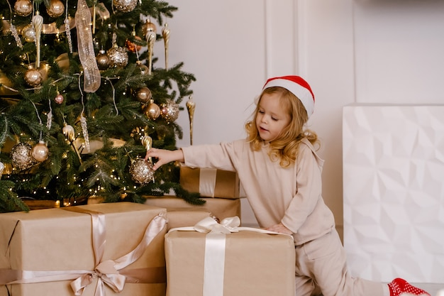 Девушка в шляпе санты с рождественским подарком под елкой. малыш с рождественским подарком дома.