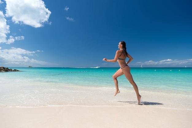 自然環境の晴れた日に白い砂浜、ターコイズブルーの水と青い空と海のビーチを走るセクシーな水着の女の子。日焼け、入浴。夏休み。休息、リラックス、アクティブなレジャー