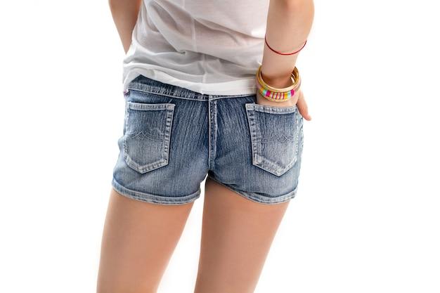 짧은 데님 반바지에 소녀입니다. 뒷주머니에 손을 넣습니다. 새로운 컬렉션의 청바지 반바지. 심플한 액세서리로 캐주얼한 옷.