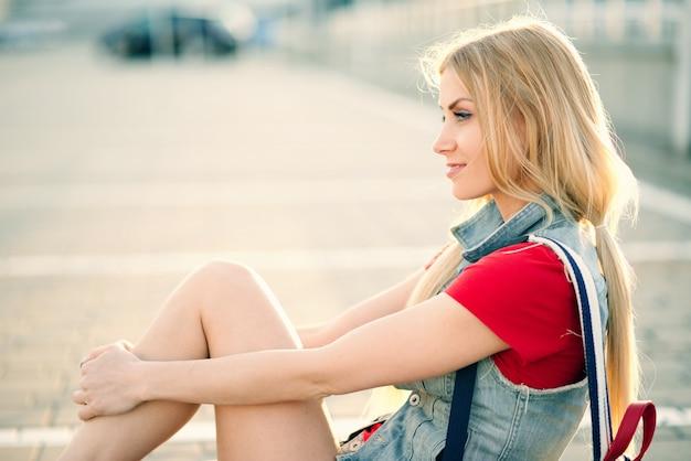 반바지와 땋은 머리 소녀는 도시에서 여름에 바닥에 앉아