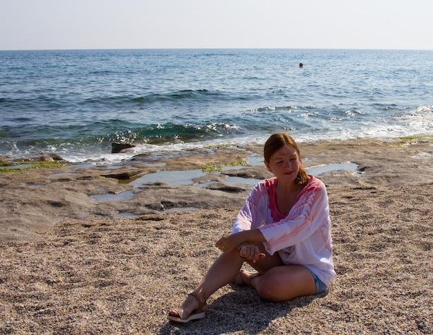 海沿いのビーチでショートパンツと白いブラウスの女の子..砂浜の赤毛の女性。南の休日