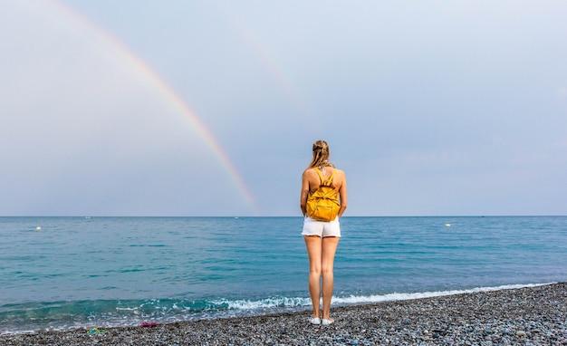 Девушка в шортах и с желтым рюкзаком на пляже наблюдает за радугой