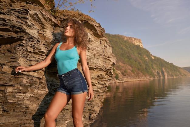 Девушка в шортах, опираясь на скалу у озера