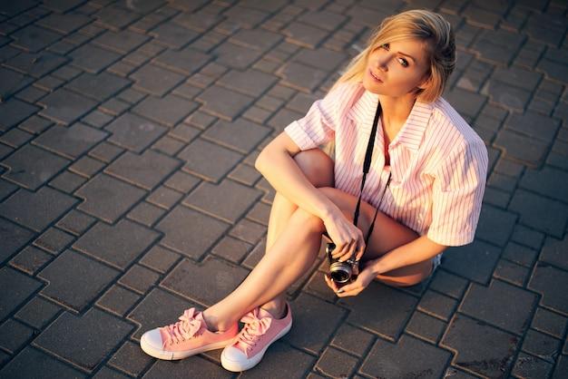 카메라 휴식과 반바지에 여자는 바닥에 앉아