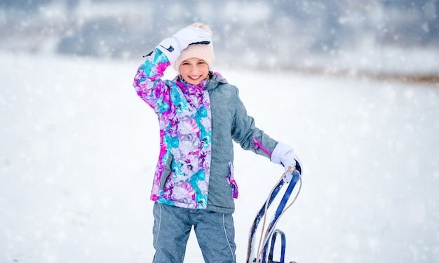 そりを保持しているスキー衣装の女の子
