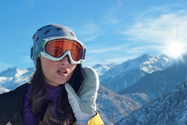 気になる表情のスキー用具を着た女の子が電話をかけます。