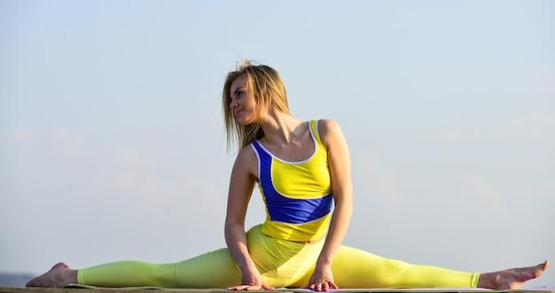 分割の女の子。屋外でストレッチするヨガ。ピラティススタジオオンライン。魅力的な若いスポーティな女性は、屋外ジムで運動しています。朝の運動。ウクライナの国民体操選手。アクロバットと体操。