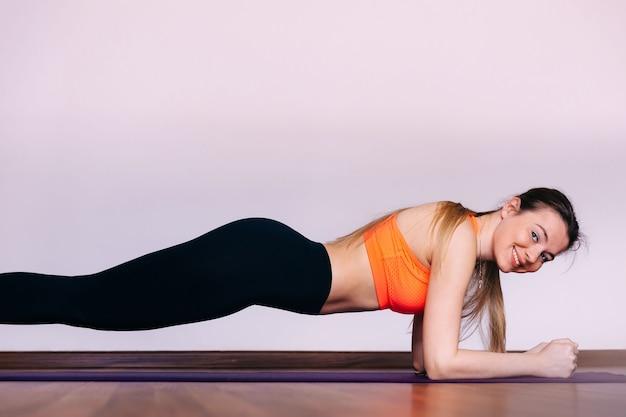 Девушка в спортивной стильной одежде стоит в позе планки или делает горизонтальные отжимания, дышит, укрепляет тело, тренируется в гостиной дома