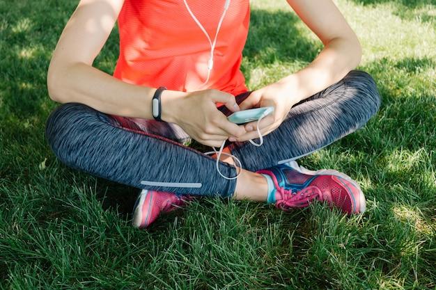 スポーツ服の女の子は夏の公園の芝生の上に座ってヘッドフォンで音楽を聴く