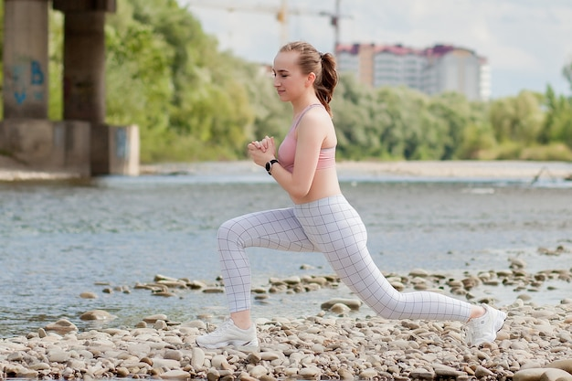 스포츠 유니폼을 입은 소녀가 강둑에 스트레칭을합니다.