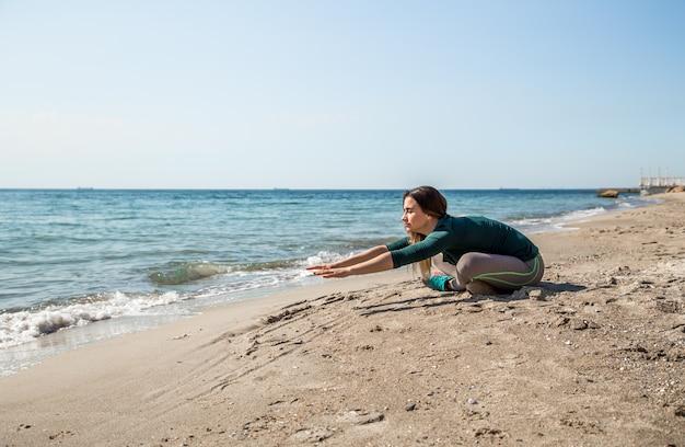 音楽、スポーツの動機、スポーツ、フィットネスを聞いて海でスポーツウェアフィットネスの女の子