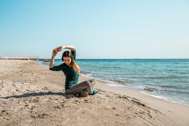 Девушка в спортивной одежде у моря слушает