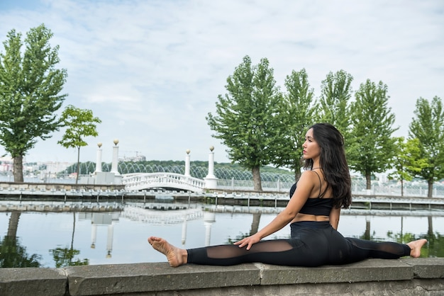 スポーツウェアの女の子は、湖、自然のそばでより糸をやってスポーツと健康的なライフスタイルに行きます