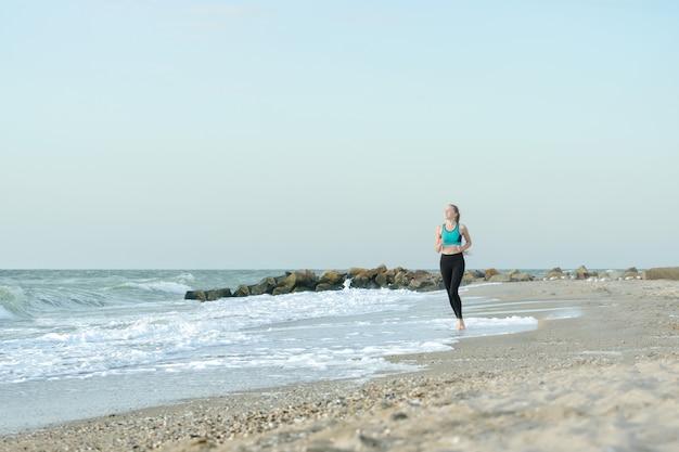 サーフィンラインに沿って実行しているスポーツウェアの女の子。