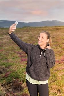 Девушка в спортивной одежде делает автопортрет с мобильным телефоном в парке на закате