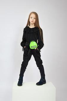 Девушка в весенних ботинках позирует в студии на белом фоне. детская мода красивая одежда