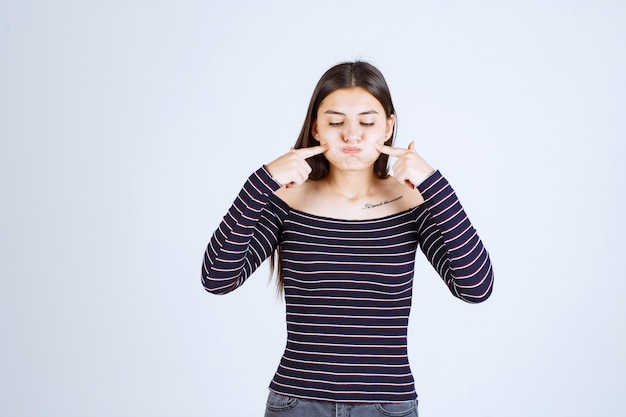 Девушка в рубашке srtiped выглядит больной и показывает рот.