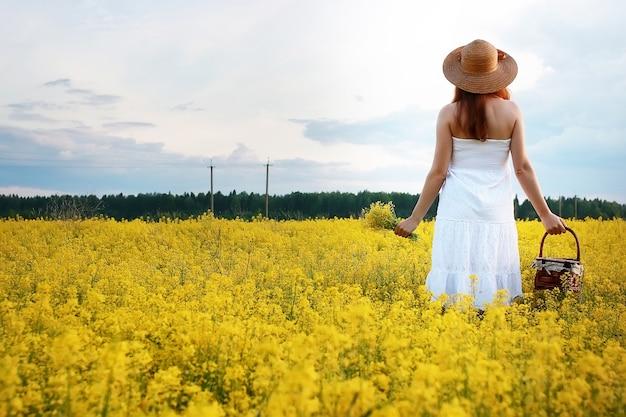 Девушка в соломенной шляпе в поле цветущих желтых цветов