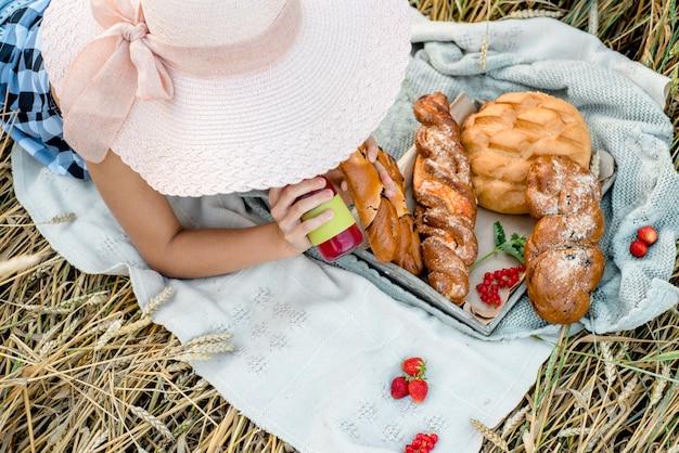 ピクニックの麦わら帽子の少女。上面図。ブレッドとフルーツ、ベリーとクロワッサンを使った屋外での美的ピクニック。