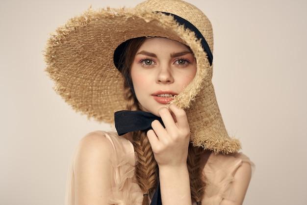 黒のリボンとベージュのドレスと麦わら帽子の女の子