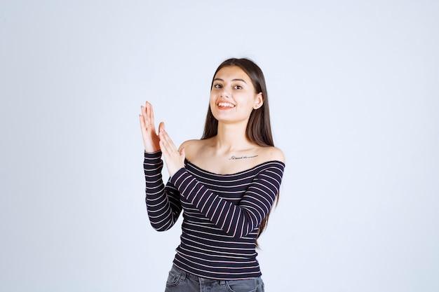 パフォーマンスを称賛する縞模様のシャツの女の子。