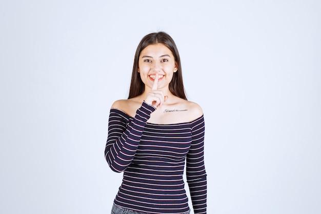沈黙を求める縞模様のシャツの女の子。