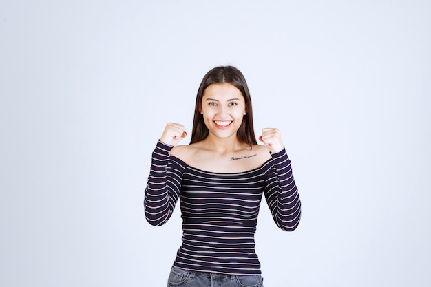 彼女の腕の筋肉を示す縞模様のシャツの女の子。