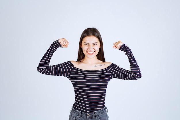 Девушка в полосатой рубашке демонстрирует мышцы рук.