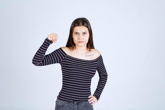 그녀의 팔 근육을 보여주는 스트라이프 셔츠에 소녀.