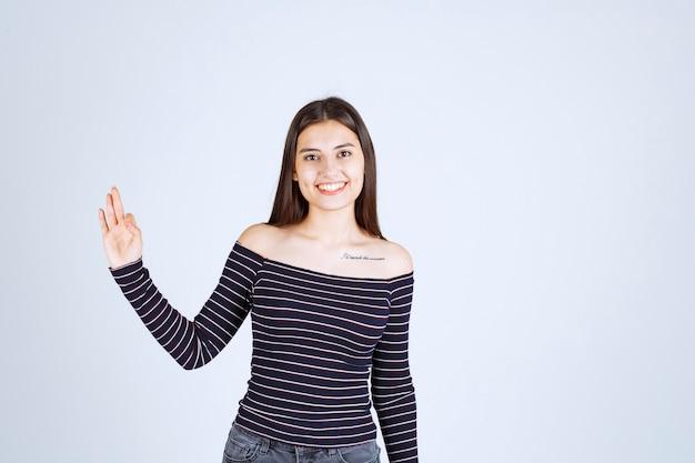 Девушка в полосатой рубашке делает знак удовольствия.