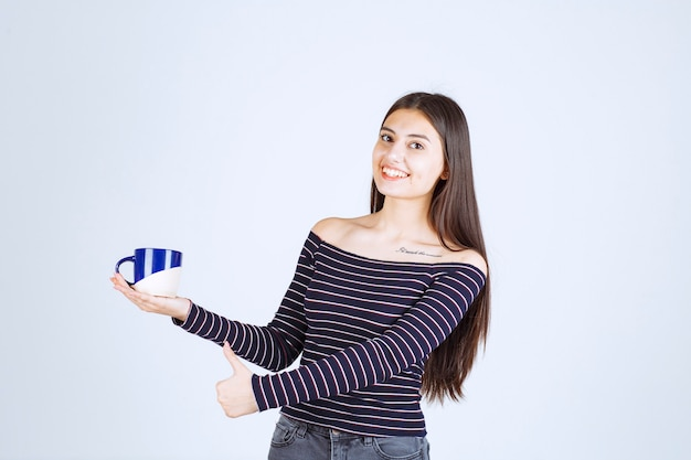 コーヒーのマグカップを保持し、楽しみのサインを示す縞模様のシャツの女の子。