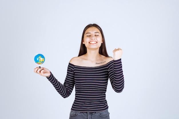 Девушка в полосатой рубашке держит мини-глобус и выглядит взволнованной.