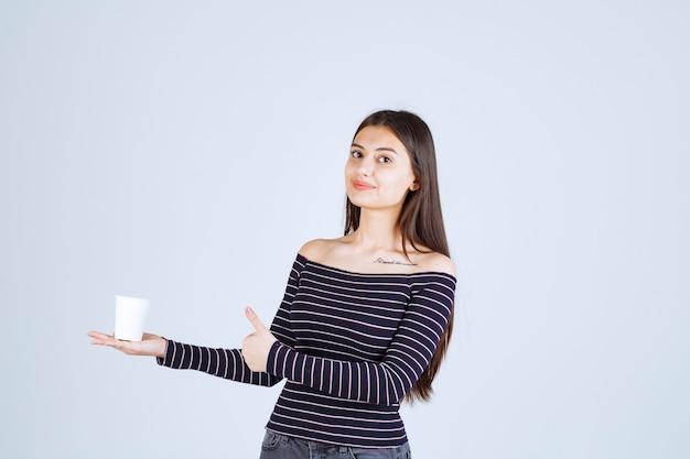 プラスチック製のコーヒーカップを持って、良い味を指している縞模様のシャツの女の子。