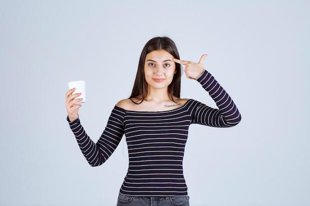Девушка в полосатой рубашке держит пластиковую кофейную чашку и думает.