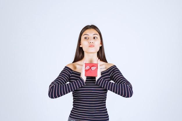 赤いギフトボックスを持っている縞模様のシャツの女の子は、混乱して疑わしいように見えます。