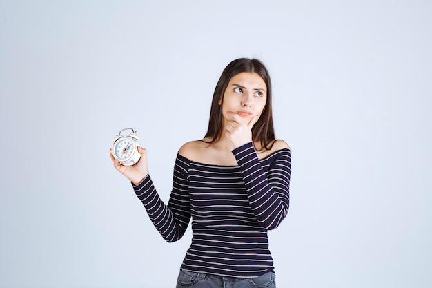 알람 시계를 들고 스트라이프 셔츠에 소녀와 겁에 질린 보인다.