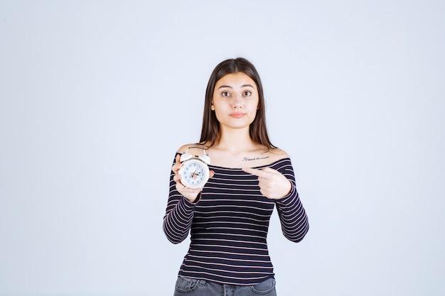 目覚まし時計を持って新商品として宣伝するストライプのシャツを着た女の子。