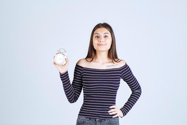 Девушка в полосатой рубашке держит будильник и продвигает его как новый продукт.