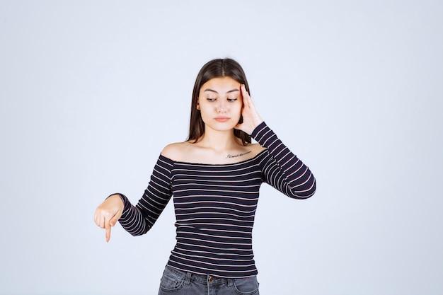 그녀가 지쳐 있거나 두통이있을 때 그녀의 머리를 잡고 스트라이프 셔츠에 소녀.