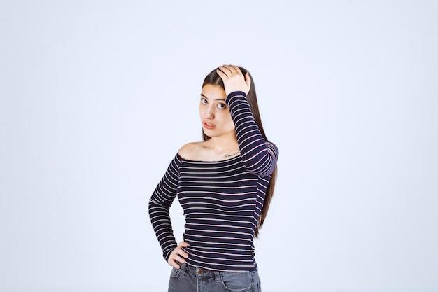 Девушка в полосатой рубашке держится за голову из-за головной боли.