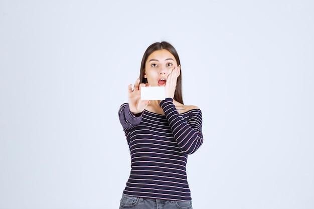 스트라이프 셔츠에 소녀는 명함을 보유하고 놀란 보인다.