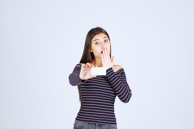 Девушка в полосатой рубашке держит визитку и выглядит удивленно.