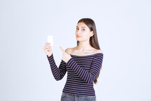 Девушка в полосатой рубашке держит визитку и указывает на нее.