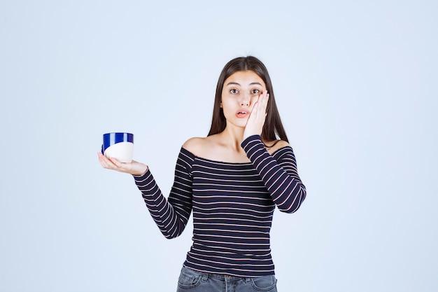 Девушка в полосатой рубашке держит чашку кофе и выглядит смущенной.